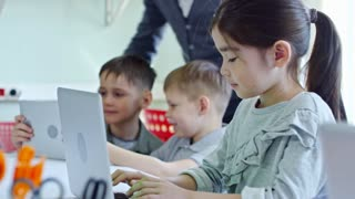 Medium shot of schoolchildren using laptop computers during information technology lesson, young male teacher helping and talking to them