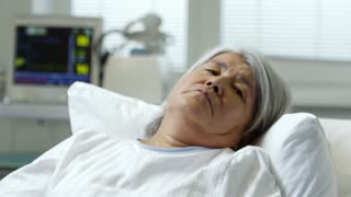 Medium shot of senior female patient lying in bed and taking medications handed by unrecognizable nurse
