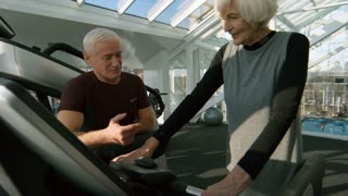 Medium shot of senior fitness trainer with grey hair explaining elderly woman how to use treadmill during workout in gym