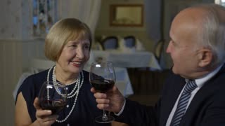 Medium shot of senior woman and elderly man holding hands and drinking wine on romantic date in restaurant
