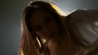 Medium shot of sensual young woman in top and mens shirt touching her hair and moving seductively before camera in dark foggy studio with bright spotlight