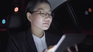 Medium shot of serious Asian businesswoman in glasses working on tablet while sitting in backseat of car driving through city at night