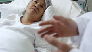 Medium shot of sick senior woman lying in bed and shaking hands with unrecognizable woman
