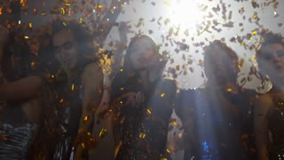 Medium shot of six partying women in sparkling sequin dresses dancing in confetti shower and looking at camera during party in nightclub