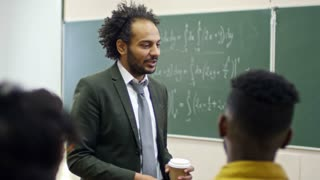 Medium shot of smiling middle eastern man holding takeaway coffee cup and talking to group of students before mathematics lesson, handheld