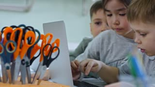 Medium shot of three schoolchildren of different ethnicities using laptop computer together when having information technology class