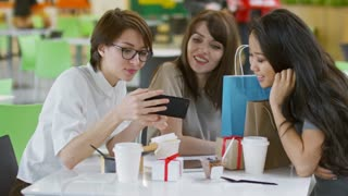 Medium shot of three young women sitting at table in cafe and talking to each other when using mobile phone