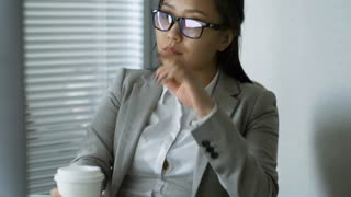 Medium shot of tired Asian businesswoman taking off glasses and drinking takeaway coffee when taking break from work in office