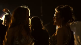 Medium shot of two ecstatic young female friends grooving and dancing to music at concert