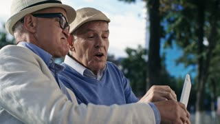 Medium shot of two elderly male friends sitting outdoors, talking to each other and using tablet computer