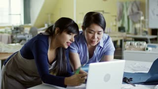 Medium shot of two multiethnic women using laptop computer and color swatches when choosing design ideas for fashion collection