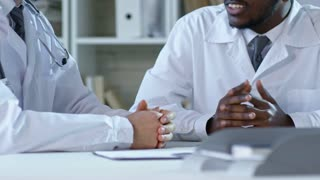 Medium shot of two people in lab coats shaking hands and talking when sitting at desk during meeting in office