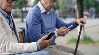Medium shot of two senior male friends in hats, one with walking stick, sitting next to each other on bench in pedestrian street and using their smartphones