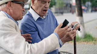 Medium shot of two senior male friends in hats, one with walking stick, sitting next to each other on bench in pedestrian street, using application on smartphones and discussing it