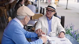 Medium shot of two senior men in hats sitting next to each other at table in street cafe and talking over cup of tea