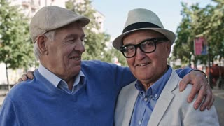 Medium shot of two senior men in hats standing in pedestrian street on warm day, hugging each other and looking at camera
