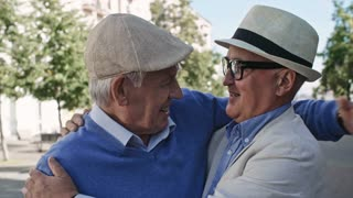 Medium shot of two senior men in hats standing in pedestrian street on warm day, hugging each other and patting on the shoulders