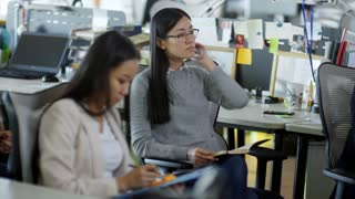 Medium shot of two young Asian women sitting in office and talking notes when listening to boss or colleague