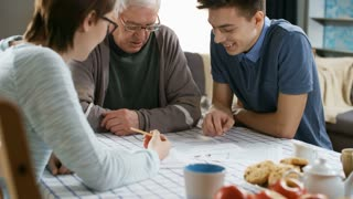 Medium shot of two young volunteers helping elderly man with household bills or explaining text of some document while sitting together at table