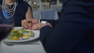 Medium shot of unrecognizable elderly man gifting engagement ring to surprised senior woman during romantic date in restaurant