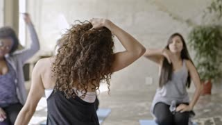 Medium shot of unrecognizable female yoga teacher with curly hair showing neck stretching exercise to multiethnic group of young women sitting on mats in studio