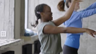 Medium shot of young African girl dancing and laughing in aerobics class