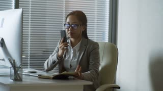 Medium shot of young Asian businesswoman in glasses taking notes in notebook when communicating with colleague or client
