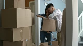Medium shot of young Asian couple looking through cardboard box and chatting while unpacking stuff in new house