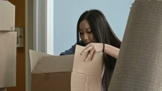 Medium shot of young Asian woman searching for something in pile of cardboard boxes with help of her husband while unpacking things in new house