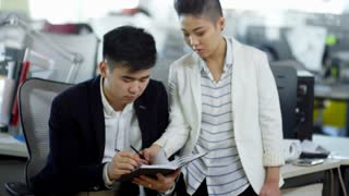 Medium shot of young Asian woman talking to male colleague and helping him with project when working in office