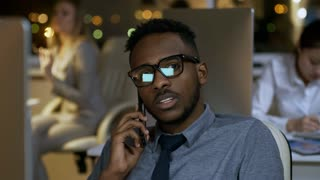Medium shot of young black employee in glasses sitting at desk in office and having phone conversation while his colleagues are working in the background