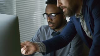 Medium shot of young black man discussing work results with mature male colleague when using desktop computer at office desk