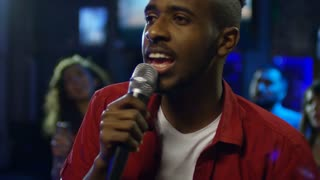 Medium shot of young black man enjoying song when singing into microphone in karaoke bar at party with friends
