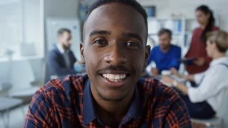 Medium shot of young black man in casual clothes sitting in front of camera at the office and smiling when having video conversation with friend or colleague
