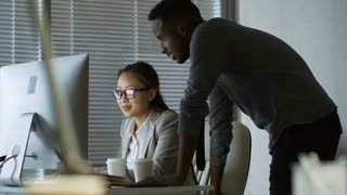 Medium shot of young black man leaning on desk of female Asian colleague when helping her with work