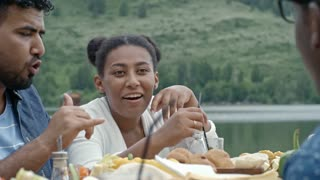 Medium shot of young black woman sitting at table by lake and talking to her friends during picnic on summer day, man gesticulating actively