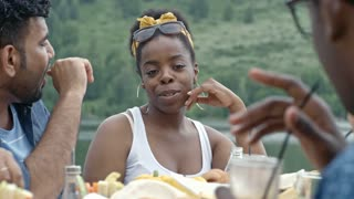 Medium shot of young black woman sitting at table by lake and telling something to her friends who are listening to her