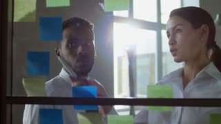 Medium shot of young businesswoman talking to black male colleague when discussing project ideas written on sticky notes attached to glass wall