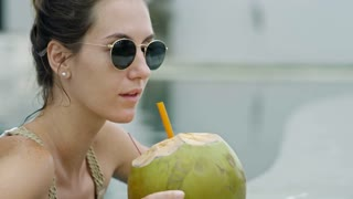 Medium shot of young Caucasian woman wearing sunglasses when relaxing in swimming pool and drinking coconut water with drinking straw