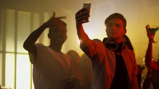 Medium shot of young male disc jockey taking smartphone selfie with group of multi ethnic people dancing with hands in the air behind him