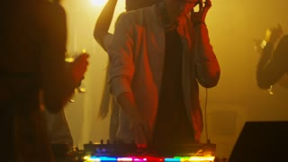 Medium shot of young male disc jockey using headphones and audio mixing console to play music for group of clubbers holding glasses with cocktails