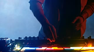 Medium shot of young male disc jockey using headphones and playing music with audio mixing console in room with blue smoke and spotlight