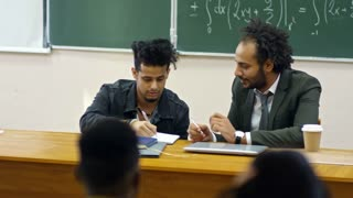 Medium shot of young male student sitting in lecture hall and discussing his work with middle aged teacher of mathematics