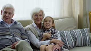 Medium shot with PAN of happy boy and girl sitting on sofa with grandparents and posing for camera