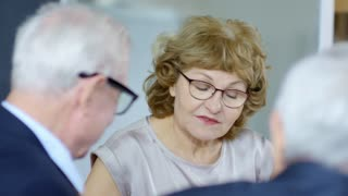 Medium shot with slow motion of serious senior businesswoman in glasses having meeting with elderly businessmen in suits: she explaining something and asking questions