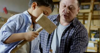 Medium shot with tilt down of middle-aged Asian man teaching little son how to use chisel and mallet while spending time with him in carpentry workshop making wooden toy
