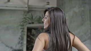 Meidum shot of laughing Hispanic woman dancing zumba in group class