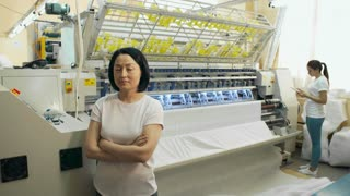 Mid-aged asian woman standing in textile factory and looking at camera while her young colleague using digital tablet and operating textile machine