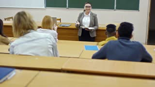 Middle aged female university teacher in glasses smiling and talking to multi ethnic group of students when asking questions during lecture
