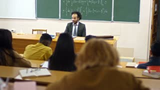 Middle aged male teacher of mathematics drinking coffee and using laptop computer at work when delivering lecture on calculus to multi ethnic group of students